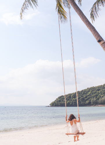 A woman on a swing with the view of a stunning beach
